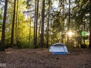 Tentje in bos met zonsondergang